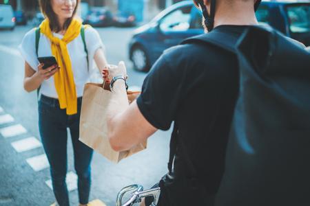 Un coursier masculin avec un vélo a livré un sac à provisions sans nom au client. Service de livraison de nourriture par coursier à domicile. Banque d'images
