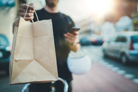 Servicio de comida rápida a domicilio anónimo. El mensajero hombre entregó el pedido sin bolsa con comida