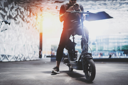 Uomo tatuato barbuto in occhiali da sole che utilizza smartphone dopo aver guidato in scooter elettrico in città.