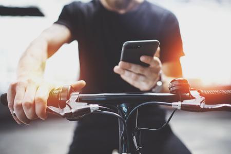Uomo hipster tatuato che tiene per mano lo smartphone e usa l'app mappe prima di guidare in scooter elettrico in città.