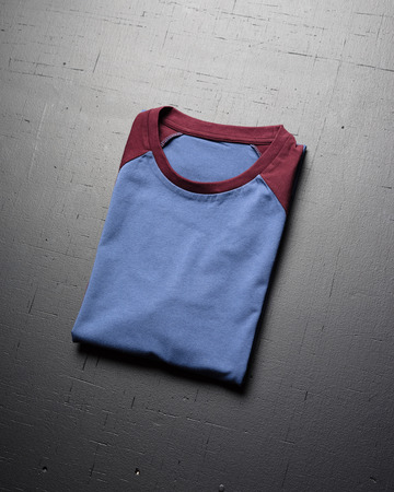 Clean vintage folded t-shirt lies on a black wooden table background. Front view of American Hipsters retro classic clothes.