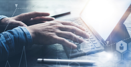 Close-up view of male hands typing on electronic tablet keyboard-dock station. Businessman working at office and using electronic pen and device. Wide format.