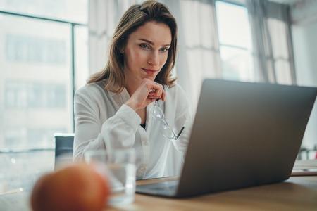 Knappe zakenvrouw die op laptop werkt op haar werkplek op modern kantoor. Onscherpe achtergrond. Stockfoto
