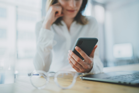 Business woman using mobile phone at working day in office.Blurred background. Business Technology Communications Mobility. Stock Photo