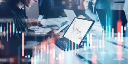 모니터에 재무 그래프와 통계가 있는 전면 노트북 컴퓨터에 앉아 있는 비즈니스 여성. 이중 노출. 넓은.