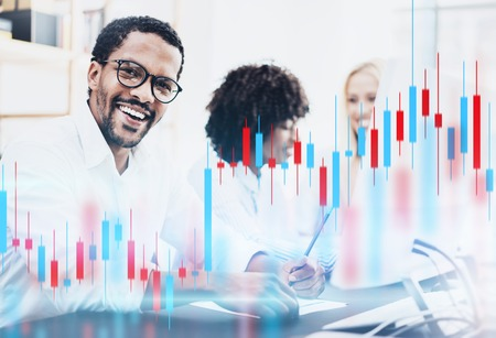 Teamwork traiding concept.African american man in white shirt smiling at the camera. Red and green candlestick chart and stock trading computer screen background. Double exposure.