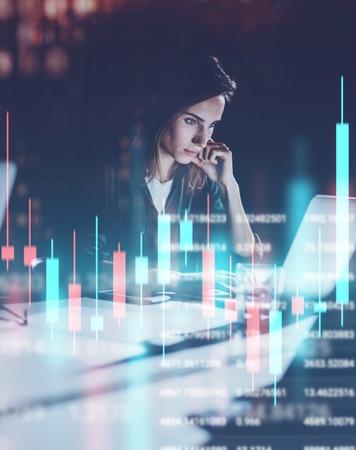 Junge Frau, die nachts modernes Büroloft arbeitet. Rotes und grünes Leuchterdiagramm und Aktienhandel auf Hintergrund. Doppelbelichtung.