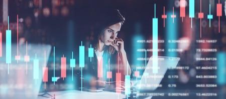 야간 현대 사무실에서 일하는 젊은 여성. 기술 가격 그래프 및 표시기, 빨간색 및 녹색 촛대 차트 및 주식 거래 컴퓨터 화면 배경. 이중 노출.와이드. 스톡 콘텐츠