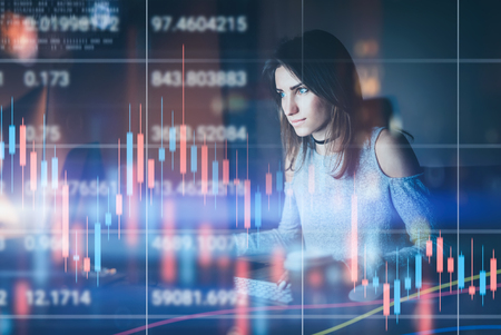 Young woman traider working at night modern office.Technical price graph and indicator, red and green candlestick chart and stock trading computer screen background. Double exposure.