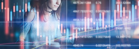 Young female model working at night modern office.Technical price graph and indicator, red and green candlestick chart and stock trading computer screen background. Double exposure.Wide. Zdjęcie Seryjne