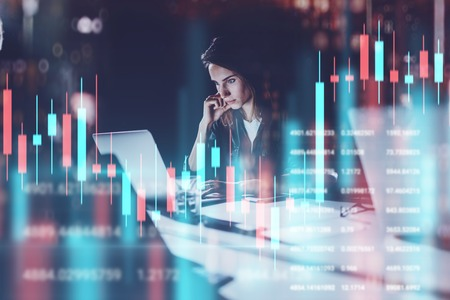 Business woman sitting at night office in front laptop computer with financial graphs and statistics on monitor. Red and green candlestick chart and stock trading on background. Double exposure.