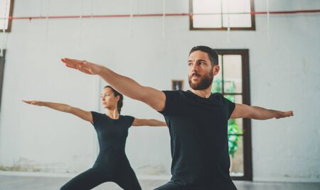 Young sportive man and woman are practicing yoga exercises in the studio. Couple of young sporty people practicing yoga lesson with partner Фото со стока