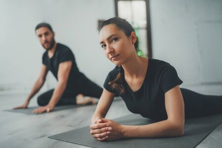 Yoga Practice Exercise Class Concept. Two beautiful people doing exercises.Young woman and man practicing yoga indoors. Фото со стока