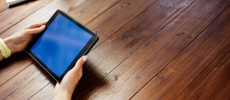 Mockup image of a woman using digital tablet with blank screen on wooden table. Close up photo of female hands with device