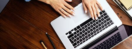 Closeup photo of female hands with a laptop on wooden table. Female freelancer connecting to internet via computer. Blogger or journalist writing new article. 写真素材