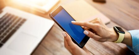 Mockup image of a woman using smartphone with blank screen on wooden table. Close up photo of female hands with mobile phone