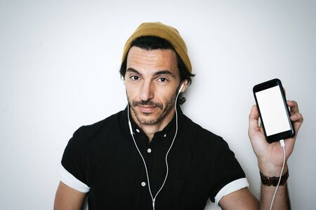 Handsome guy showing his smartphone with blank screen