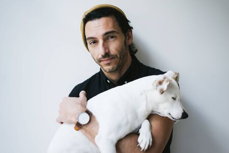 Studio portrait of a handsome guy with his dog