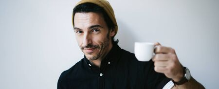 Portrait of an attractive guy with cup of coffee