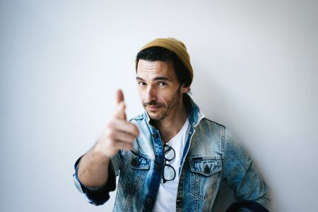 Portrait of a handsome guy pointing his finger at you