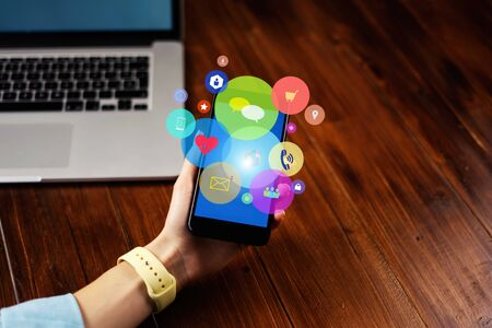 Close-up photo of female hand holding smartphone with media and social networks icons. Concept of digital network 写真素材 - 138816843
