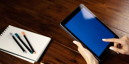 Mockup image of a woman using digital tablet with blank screen on wooden table. Close up photo of female hands holding device upright 写真素材 - 138111611