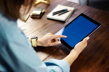 Mockup image of a woman using digital tablet with blank screen on wooden table. Close up photo of female hands holding device upright 写真素材 - 138111951