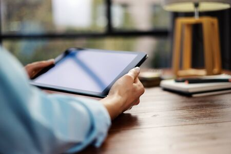 Woman pointing on digital tablet screen, chatting in social networks, meeting website, searching internet, sending sms, using text messenger or online banking. Close up of female hands holding device