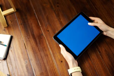 Mockup image of a digital tablet with blank screen on wooden table. Close up photo of female hands holding device horizontally 写真素材 - 138110357