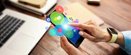 Close-up photo of female hand holding smartphone with media and social networks icons. Concept of digital network