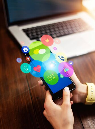 Close-up photo of female hand holding smartphone with media and social networks icons. Concept of digital network 写真素材 - 138110974