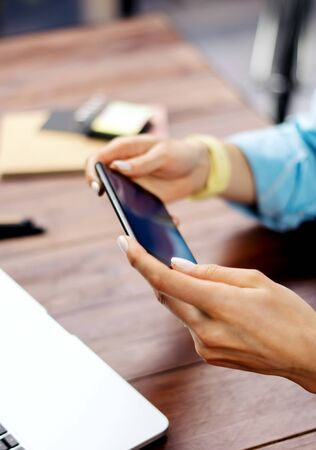 Woman pointing on smartphone screen, chatting in social networks, meeting website, searching internet, sending sms, using text messenger or online banking. Close up of female hands with mobile phone