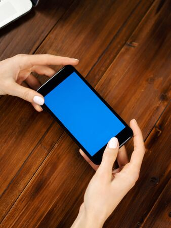 Mockup image of a woman using mobile phone with blank screen on wooden table. Close up photo of female hands holding smartphone horizontally