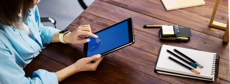 Mockup image of a woman using digital tablet with blank screen on wooden table. Close up photo of female hands holding device upright