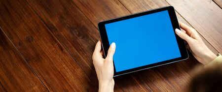 Mockup image of a digital tablet with blank screen on wooden table. Close up photo of female hands holding device horizontally