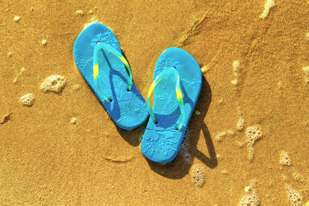 blue sandals on the beach , the concept of rest on the sea.