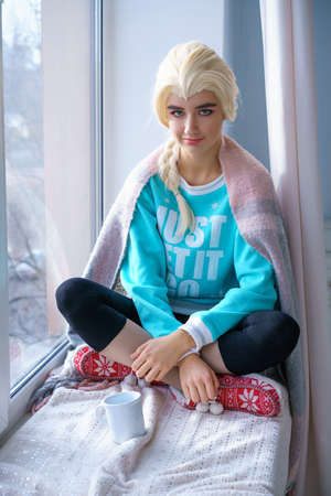 a beautiful blonde girl in a blue sweater and new year's slippers sits on the windowsill with a mug next to it in the winter time
