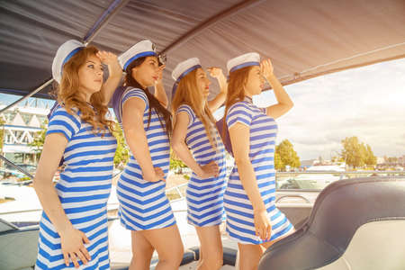 Young women in striped dresses and caps, on the deck of a yacht, the concept of recreation on a yacht.