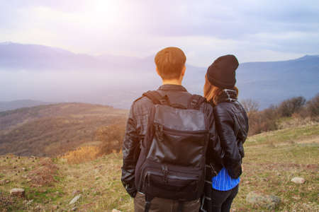 A guy with a backpack and a girl looking at the mountains in the distance, the concept of tourism.