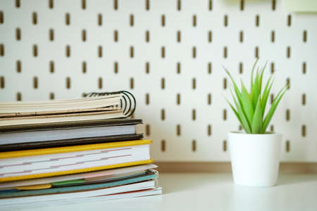 Desktop stack of notebooks and  flower in the background, soft focus. Stock fotó
