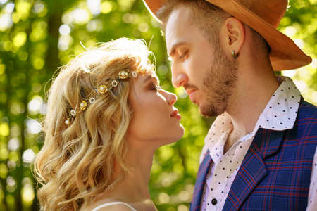 a young couple in love looks into each other's eyes, a girl with short hair stands with a guy in a hat against the background of a forest