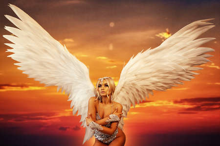 A beautiful young woman with angel wings, in silver lingerie. Background of the sunset sky.