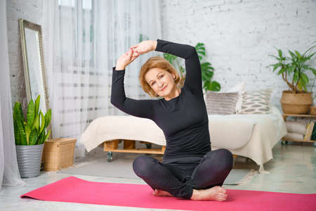 Senior woman exercising while sitting in lotus position. Active mature woman doing stretching exercise in living room at home..