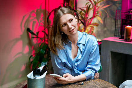 Portrait of a happy woman sitting at a table in a blue shirt in a cafe.