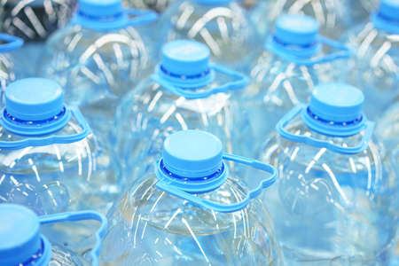 Five-liter plastic drinking water bottles close-up, soft focus. Stock fotó