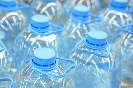 Five-liter bottles of drinking water close-up, soft focus.