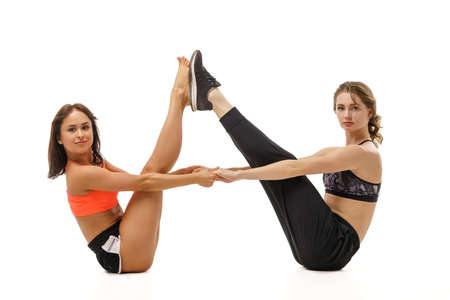 Two young girls are engaged in stretching on a white background.