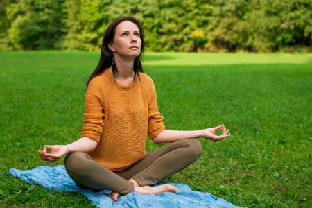 A lovely woman meditates sitting on the green grass in the Park.