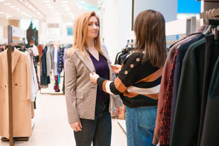 Two women choose clothes in a store.