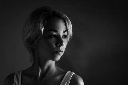 Female portrait close-up looks away, black and white photo dark. Banco de Imagens